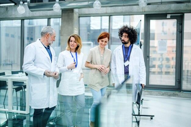 Vista frontale di un gruppo di medici che camminano nel corridoio durante una conferenza, parlando.