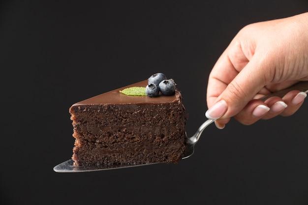 Vista frontale della mano che tiene la fetta di torta al cioccolato