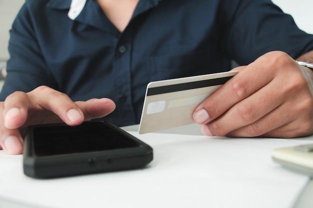 Vista frontale mano che tiene la carta di credito o bancomat e touch smartphone con schermo nero. concetto di lavoro. concetto di pagamento digitale. conto o finanziario. acquisto o concetto di acquirente. acquisti online.