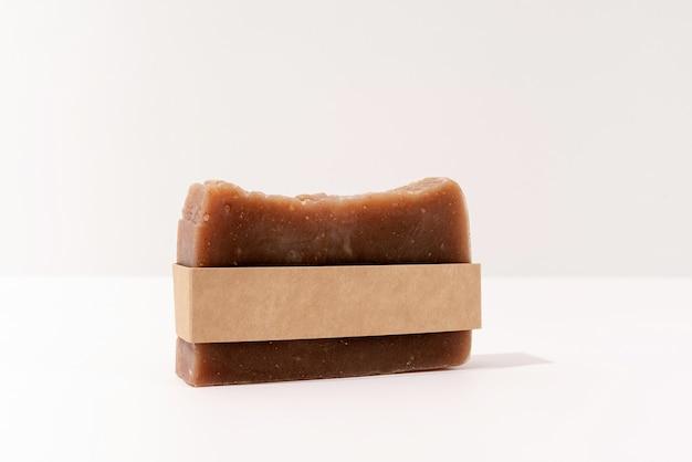 Vista frontale del sapone fatto a mano e della fascia artigianale per il design mock up su sfondo bianco