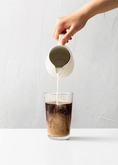 Vista frontale della mano versando il latte nel bicchiere di caffè