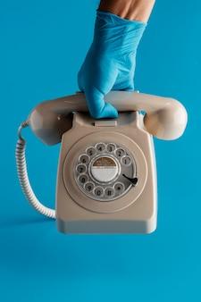 Vista frontale della mano con il guanto che tiene il telefono con il ricevitore