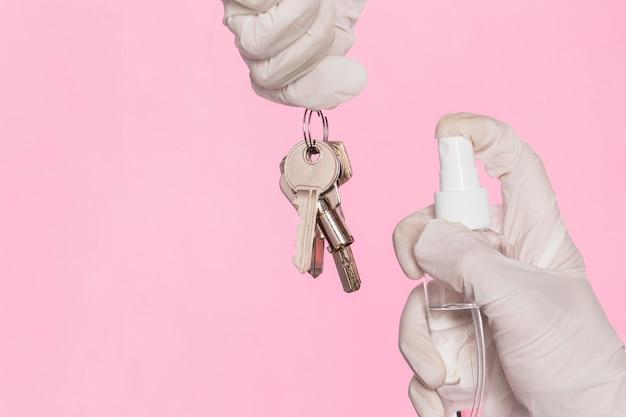 Vista frontale delle mani con guanti chirurgici disinfettando le chiavi