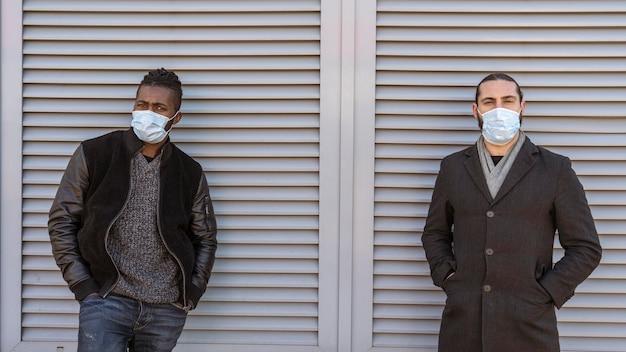 Vista frontale di uomini belli che indossano maschere mediche