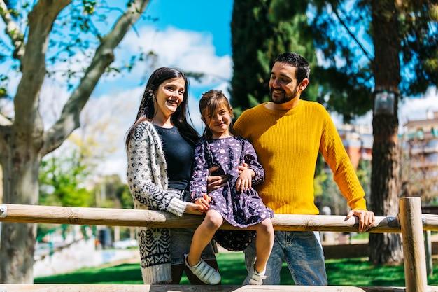 Vista frontale di una famiglia felice nel parco. padre madre e figlio insieme in natura