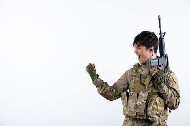 Vista frontale del soldato maschio felice con la mitragliatrice in mimetica sul muro bianco
