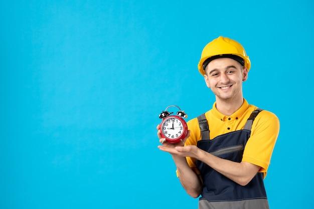 Vista frontale del lavoratore maschio felice in uniforme con orologi sulla parete blu