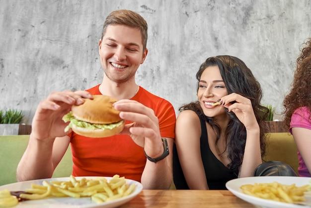 Vista frontale delle coppie felici che mangiano alimenti a rapida preparazione in caffè