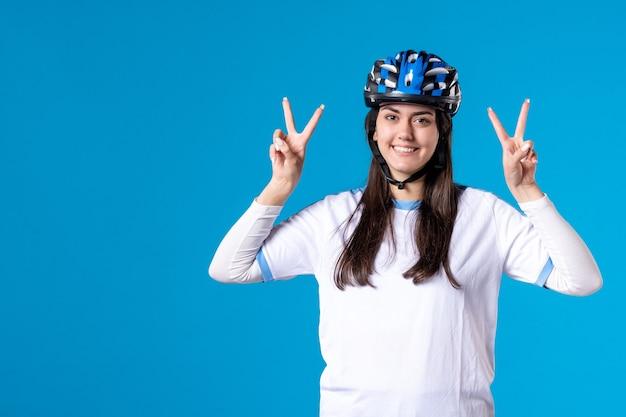 Giovane femmina felice di vista frontale in vestiti di sport con il casco