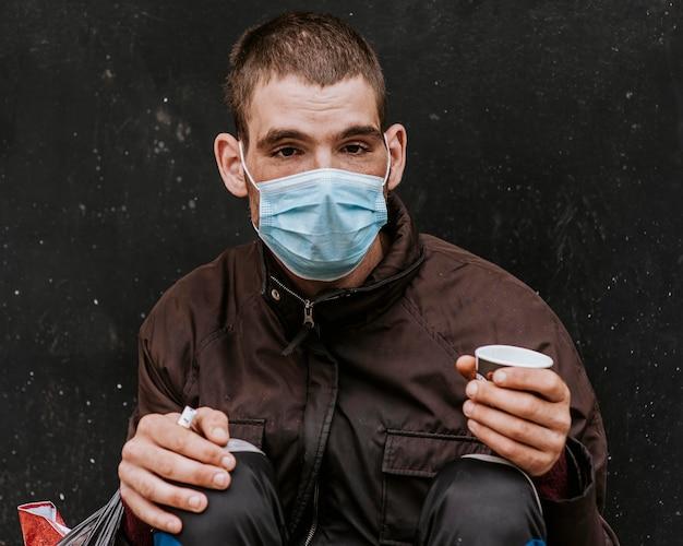 Vista frontale di un senzatetto con mascherina medica all'aperto e tazza