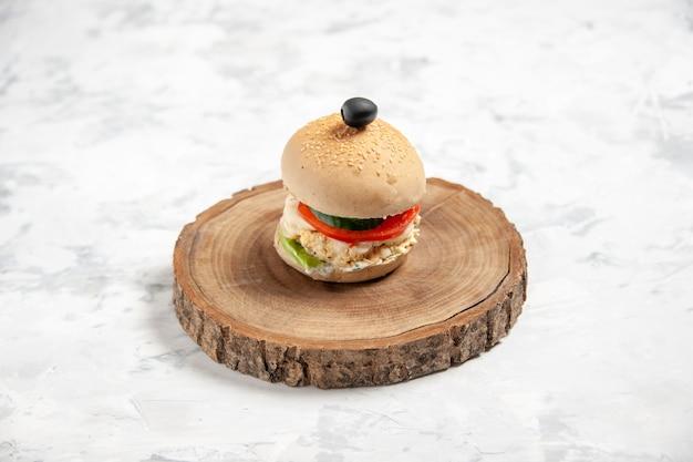 Vista frontale del delizioso panino fatto in casa con oliva nera su tagliere di legno su superficie bianca macchiata con spazio libero free