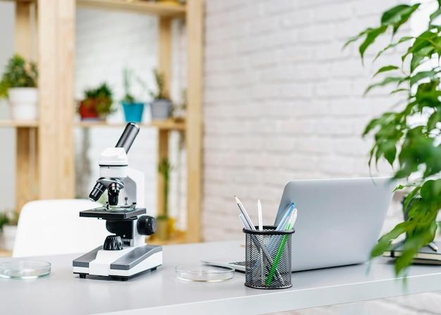 Vista frontale della scrivania del laboratorio con microscopio e laptop