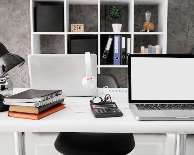 Vista frontale di laptop con notebook e calcolatrice sulla scrivania in ufficio