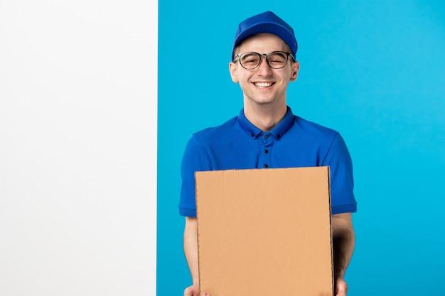 Vista frontale del corriere maschio di risata in uniforme blu con pizza sulla parete blu