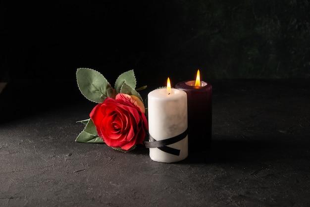 Vista frontale delle candele accese con fiore rosso su fondo nero