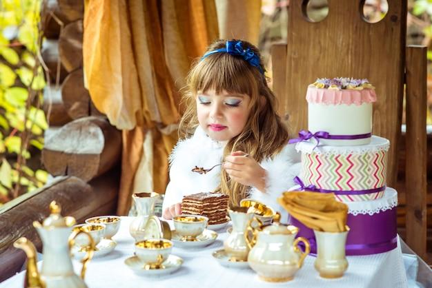 Vista frontale di una bella bambina in possesso di un pezzo di torta su un cucchiaio al tavolo