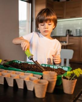 Vista frontale del ragazzino che pianta i raccolti a casa