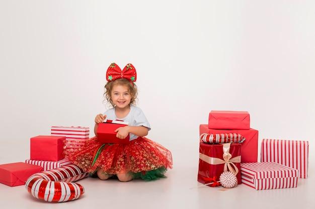Vista frontale piccolo bambino circondato da elementi di natale Foto Premium