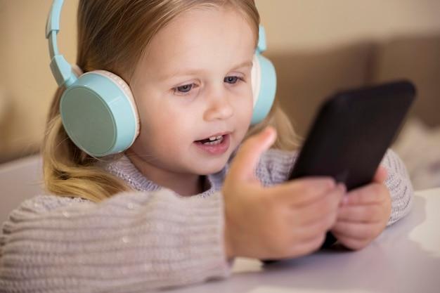 Vista frontale della bambina con cuffie e telefono