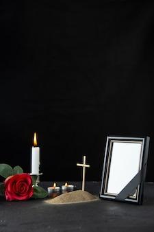 Vista frontale della piccola tomba con candela e cornice su nero