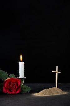 Vista frontale della piccola tomba con candela rosa rossa su nero