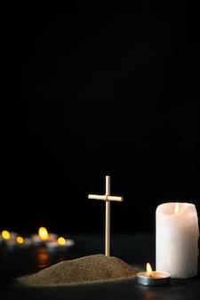Vista frontale della piccola tomba con candele sul nero