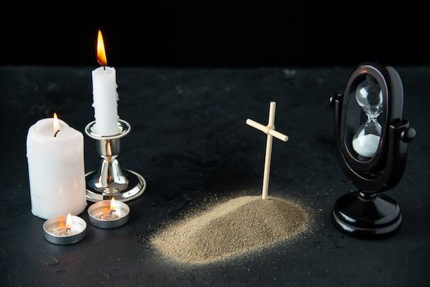 Vista frontale della piccola tomba con clessidra e candele al buio