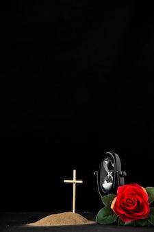 Vista frontale della piccola tomba con clessidra e rosa rossa su fondo nero