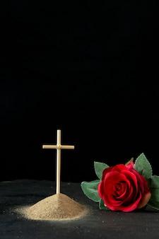 Vista frontale della piccola tomba con fiore rosso su fondo nero