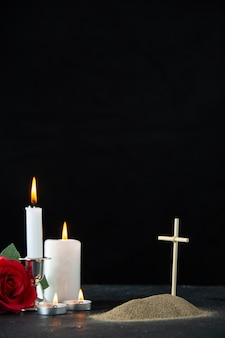 Vista frontale della piccola tomba con rosa rossa e candele su fondo nero