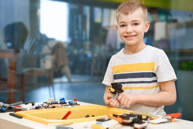 Vista frontale del ragazzo caucasico adorabile che sorride e che guarda direttamente. kit di costruzione per bambini sul tavolo, bambini che creano giocattoli