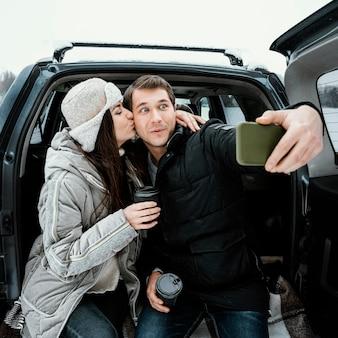 Vista frontale delle coppie amorose che prendono selfie durante un viaggio su strada