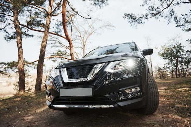 Vista frontale dell'automobile moderna nera di lusso parcheggiata all'aperto nella foresta