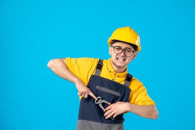 Costruttore maschio di vista frontale in uniforme e casco con le pinze sull'azzurro