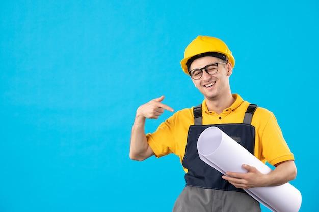 Costruttore maschio vista frontale in uniforme con piano di carta sul blu
