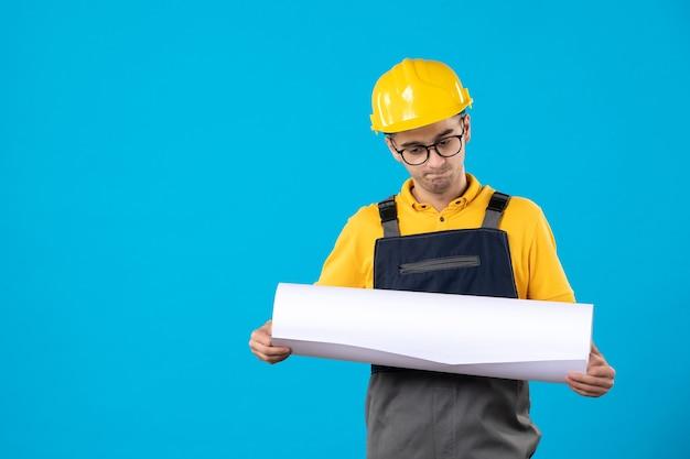 Costruttore maschio di vista frontale nel piano di lettura uniforme giallo sull'azzurro