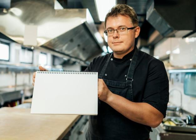 Vista frontale del cuoco unico maschio che tiene il calendario