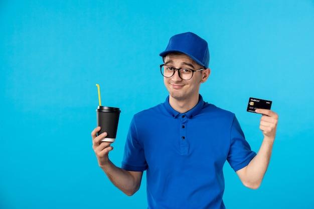 Vista frontale del corriere maschio in uniforme blu con caffè e carta di credito sul blu
