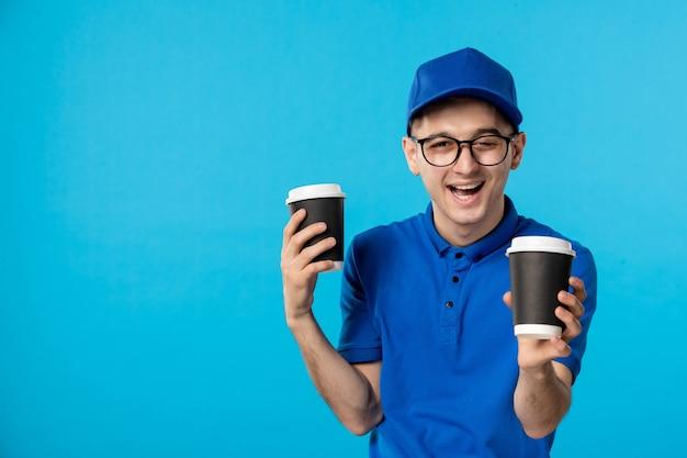 Vista frontale del corriere maschio in uniforme blu con tazze di caffè blu
