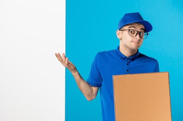 Vista frontale del corriere maschio in uniforme blu con scatola pizza sul blu