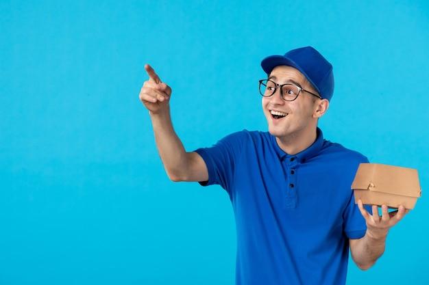Corriere maschio di vista frontale in uniforme con il pacchetto di consegna del cibo sul blu
