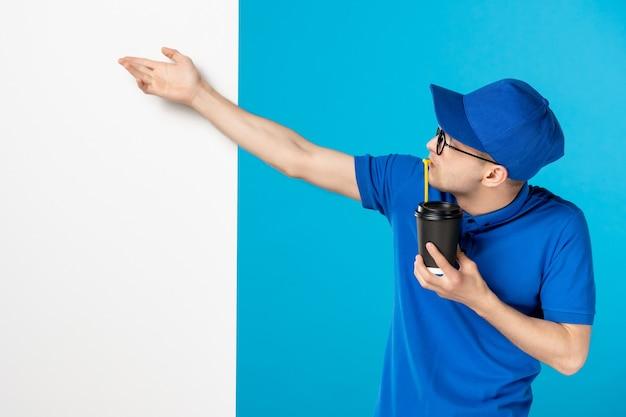 Vista frontale del corriere maschio con caffè sull'azzurro