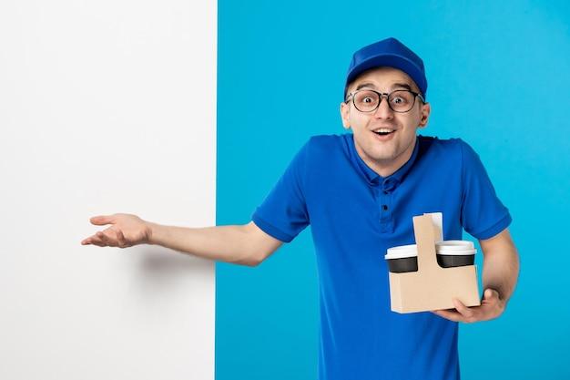 Vista frontale del corriere maschio con consegna caffè sull'azzurro