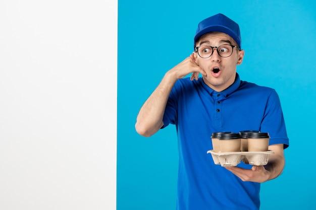 Corriere maschio di vista frontale con caffè di consegna sull'azzurro