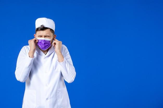 Vista frontale del medico maschio in tuta medica e maschera viola sull'azzurro