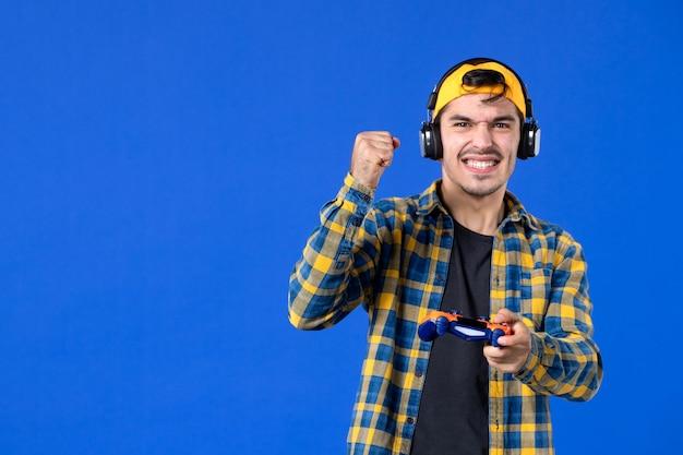 Vista frontale del giocatore maschio con gamepad e cuffie che giocano a videogiochi sulla parete blu