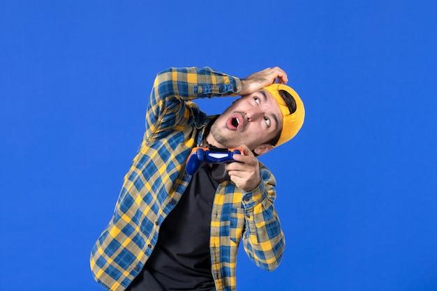 Vista frontale del giocatore maschio con gamepad che gioca al videogioco e guarda sopra sul muro blu
