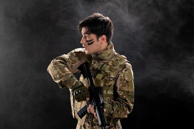 Vista frontale del soldato maschio in mimetica sul muro scuro