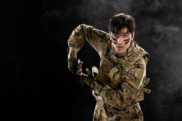 Vista frontale del soldato maschio in mimetica con pistola sul muro nero
