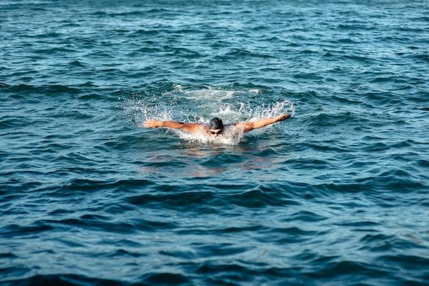 Vista frontale del nuotatore maschio che nuota in acqua